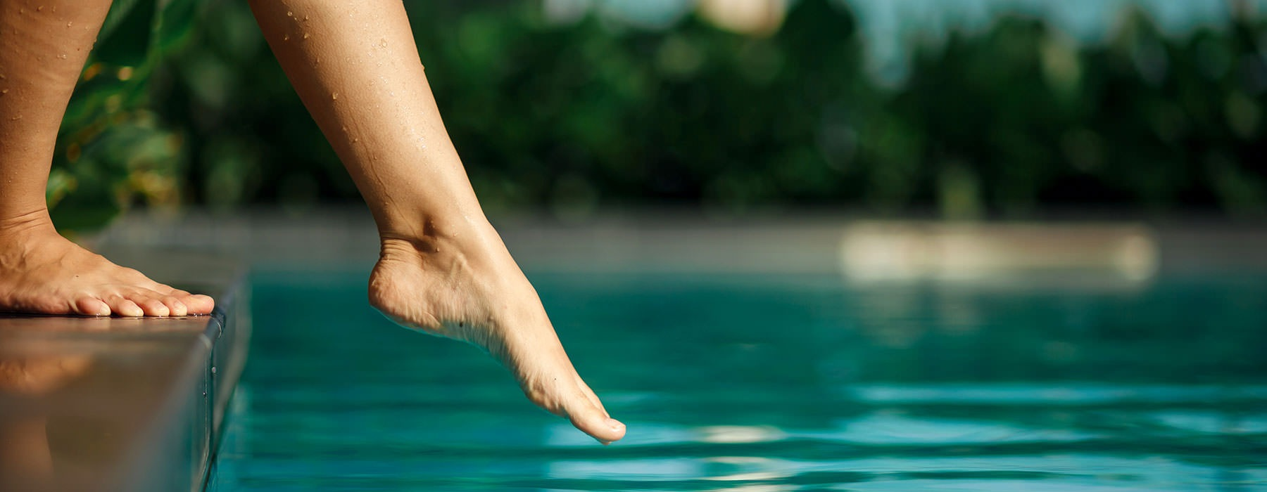 lifestyle image of a woman dipping her feet into a pool