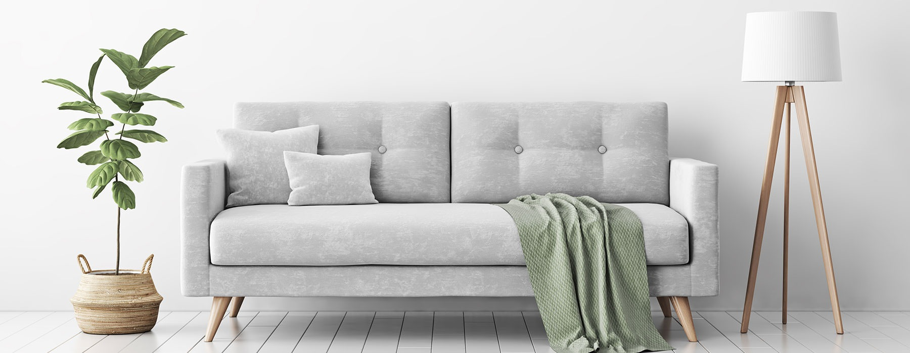 lifestyle image of a couch beside a plant and a lamp